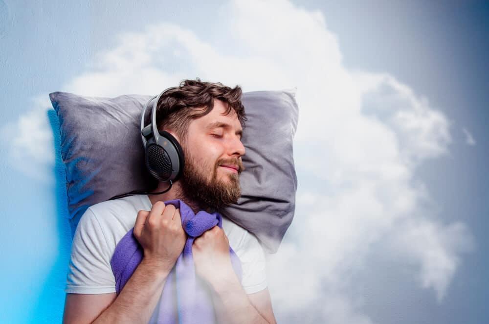 best noise cancelling headphones for sleep concept man with headphones sleeps against a cloud