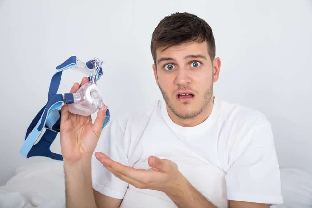A young man holds his CPAP mask with a confused face.