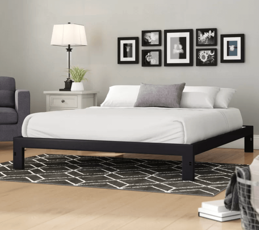 A black steel bed frame with white sheets and gray and white pillows against a wall with pictures.
