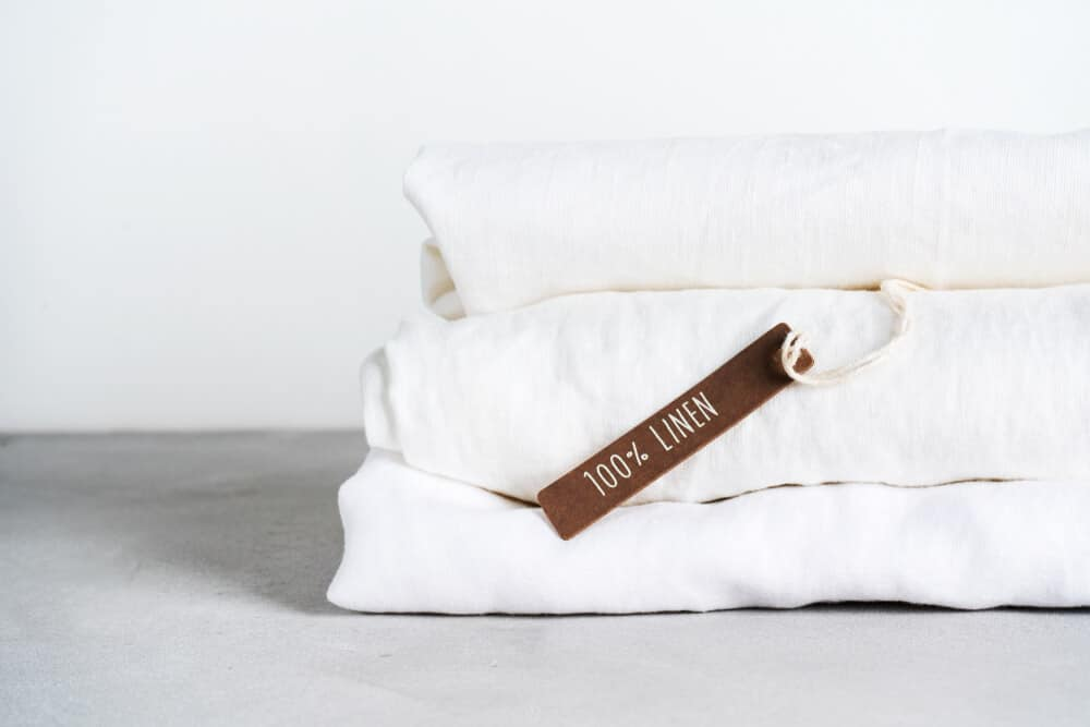 A white folded stack of flax linen sheets.