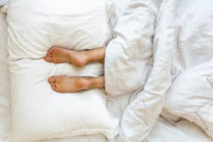 Two feet resting on two white bed pillows underneath white bed covers.