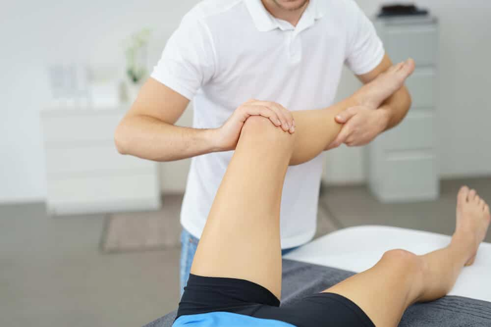 A physical therapist stretching a patient's leg on a bed.