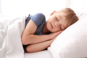 A child in a blue shirt sleeping on a white pillow with a white blanket.