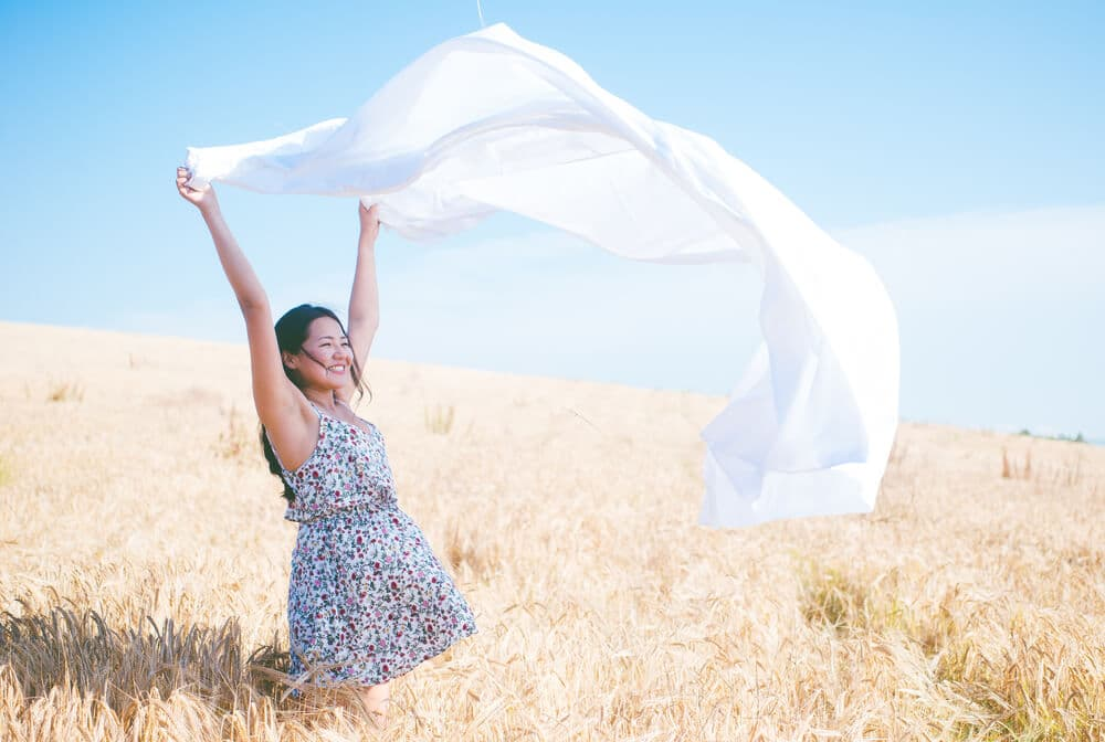 A woman holds a sheet above her head in a field on a sunny day.