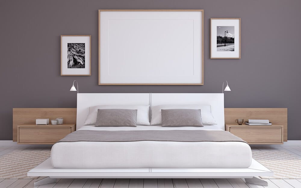 A white bed frame against a dark gray wall.