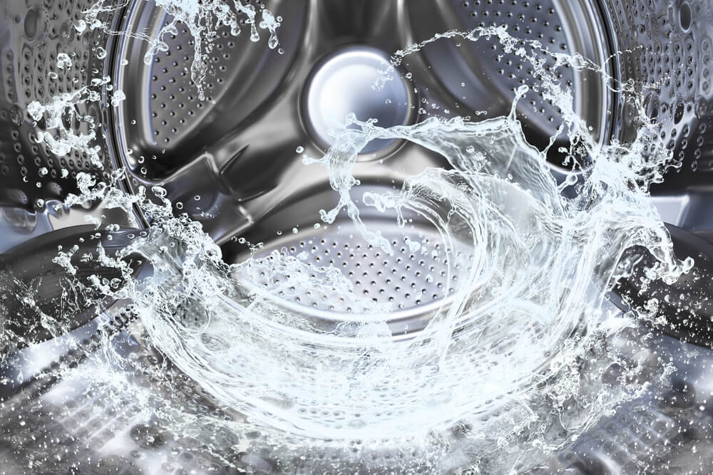 The inside metal barrel of a washing machine filled with water.