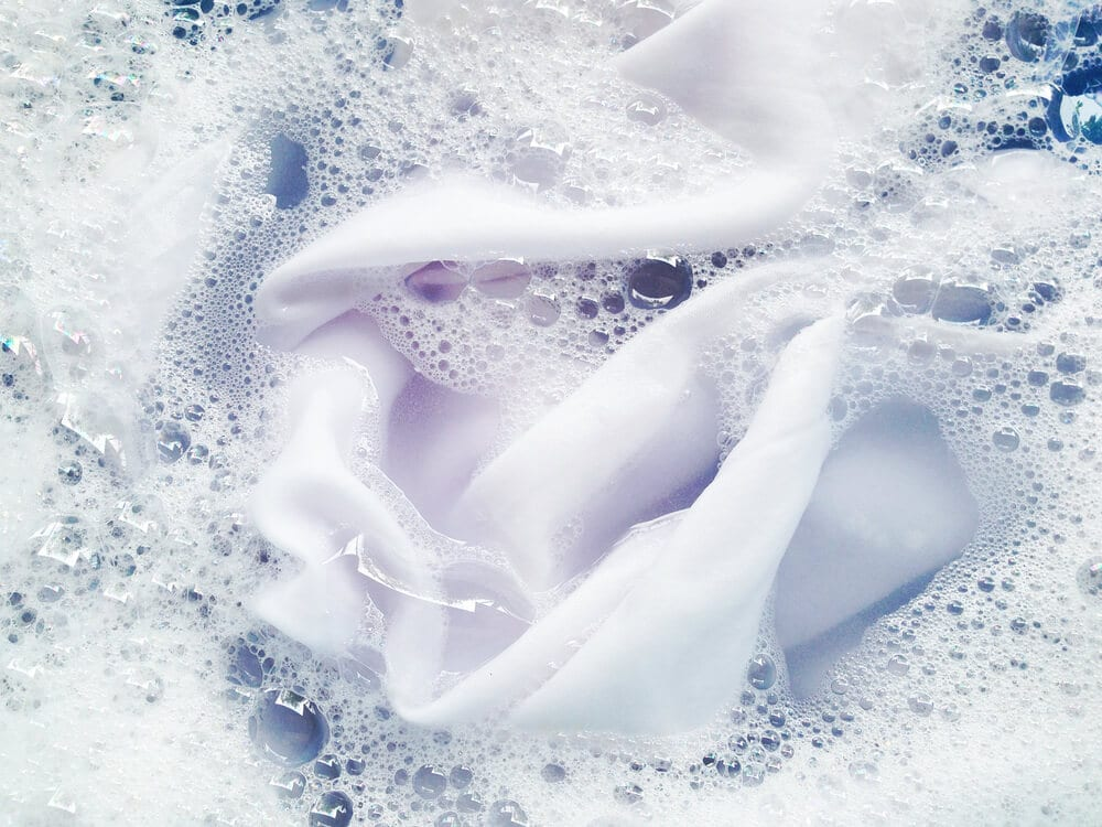 A white silk sheet soaks in soapy water.