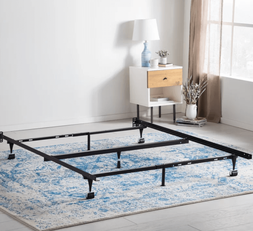 A black steel bed frame with wheels on a blue textured carpet.
