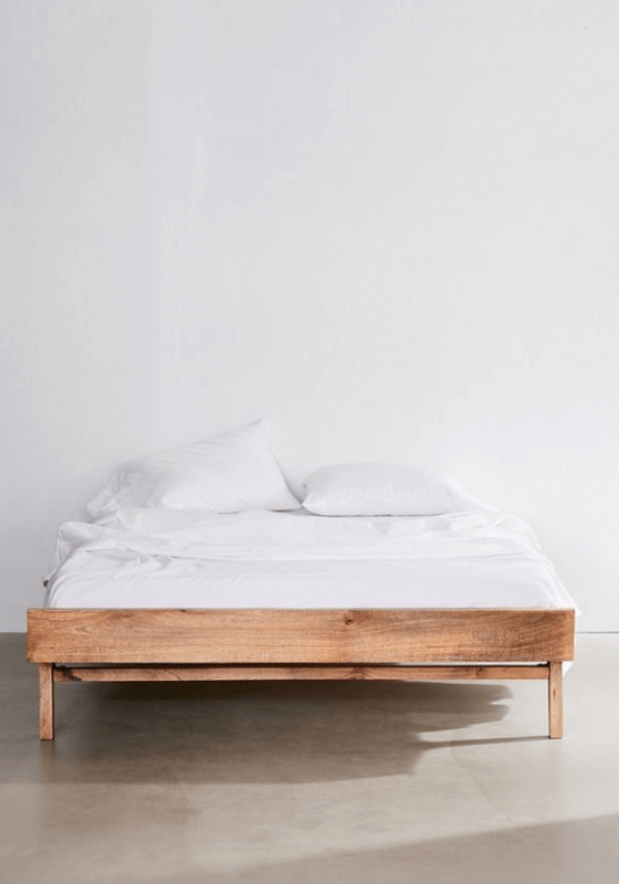 A light brown wooden bed frame with white bed sheets and two white pillows.