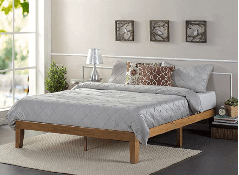 A wooden bed frame with gray bed sheets and multiple bed pillows.