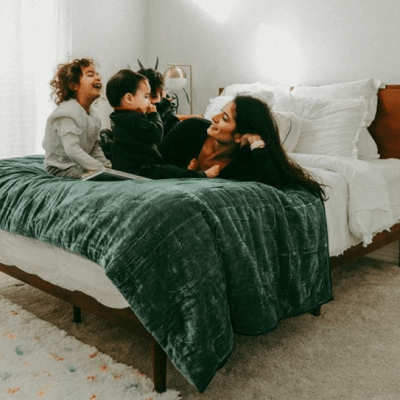 A woman and her children rest on top of a Zinus mattress.