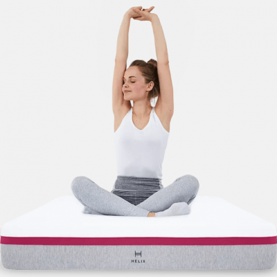 A woman sits cross-legged on a Helix mattress with her arms up.