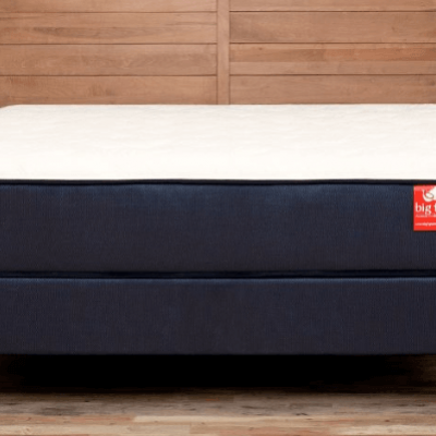 A white mattress with a red tag sitting on a wood bed frame.