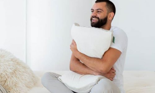 A Man smiling and hugging an Avocado pillow.