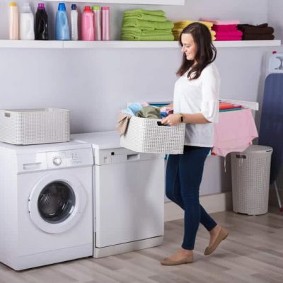A woman carries a load of laundry to her washing machine.