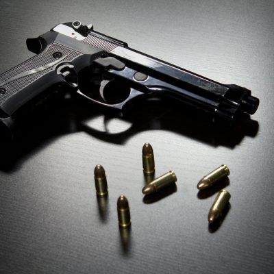 A black gun with five bullets sitting on a surface.