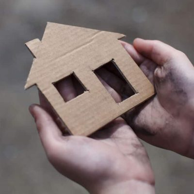 A homeless youth holding a cardboard house with a cut-out window and door.