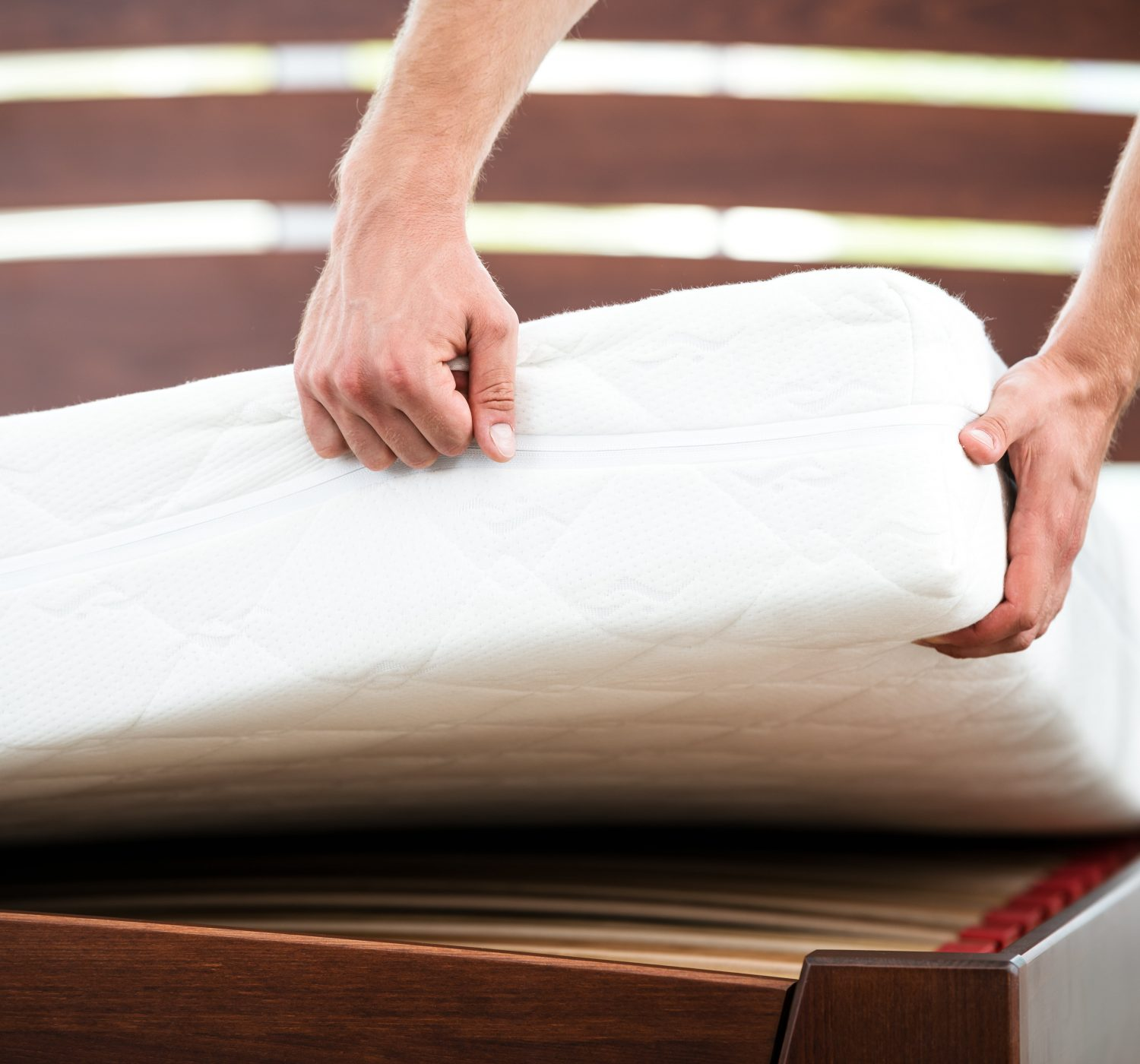 Two hands laying a white mattress on a brown slatted bed frame.